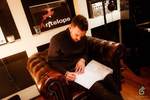 Un homme écrit dans un carnet, dans un des studio de production de Bababam, éditeur - diffuseur et producteur de podcast de marque